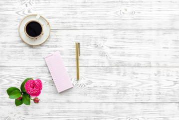 Home work desk, feminine workplace. Notebook and stationery near pink flowers and coffee on white wooden background top view copy space