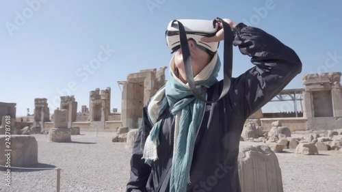 Tourist looking 3D reconstruction of Persepolis with VR headset