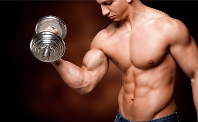 Portrait of a handsome muscle man with dumbbell posing isolated Fototapete