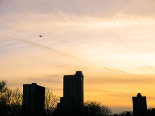 A commercial jet plane flies over residential condominium high rise buildings and trees along Lake Shore Drive and Lake Michigan in Chicago at sunset with beautiful orange cloudy sky beyond.