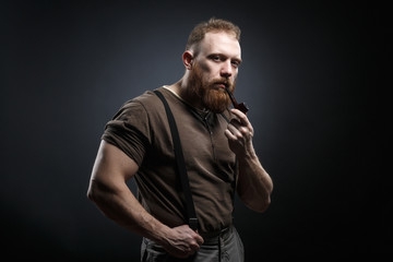 Lumberjack brutal red beard muscled man in brown shirt with smoking tube standing on dark background