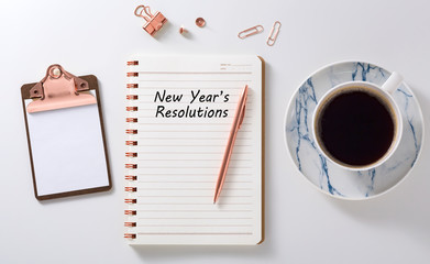 New year resolutions on notebook with coffee cup