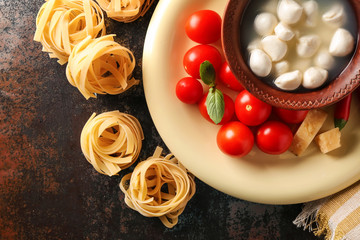 Uncooked noodles with fresh products on dark table