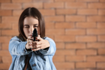 young woman pointing a gun at viewer against brick background