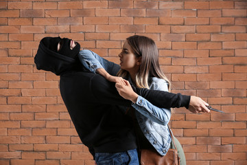 Young woman defending herself from attack by male bandit against brick background