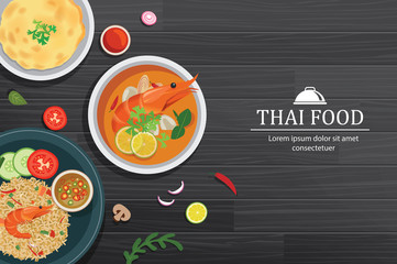 Tom yum kung in the bowl on black wood table top view. Thailand set food background.