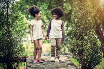 Happy little boy and girl in the park. Two African American children together in the garden.