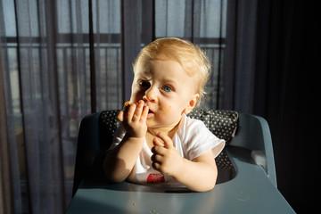 Feeding a baby in a highchair. Food Dirty Kid