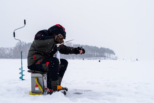 Winter fishing. Ice fisherman fishing on the lake in the cold winther day