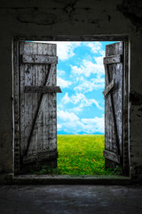 Open wood door in abandoned house. Green sunny meadow outside.