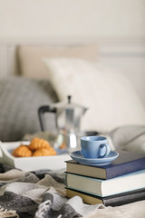 Breakfast in bed. On a white tray there is a coffee maker, coffee blue cup and croissants.