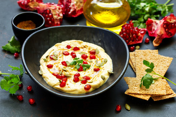 Traditional hummus, with pomegranate and cereal loaves. selective focus.