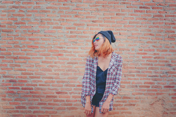 Happy young hipster woman standing against brick wall in town street.