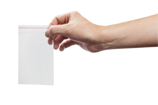 Hand holding empty plastic ziplock bag, isolated on white background