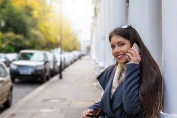 Portrait einer jungen Frau in London mit einem Handy in der Hand; Urbane Stadtfrau vor Viktorianischen Häusern in London