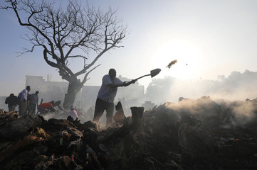 A trader uses a shovel as he attempts to recover his merchandise within the smouldering remains of clothing stalls after an overnight fire at the Bakara market in Mogadishu