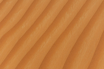 The design of the rippling textured sand dunes background in the beautiful sunshine in the United Arab Emirates.