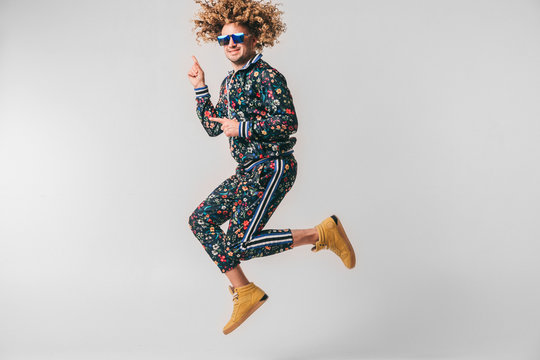 Adult positive smiling funky man with curly hair style in suglasses and vintage clothes posing on white studio background. Funny portrait of stylish male person. 80s fashion. Unusual eccentric guy.