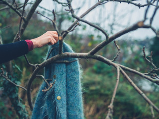 Woman picking up jumper hanging from tree