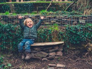 Happy little toddler on bench in garden