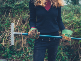 Young woman with rake in garden