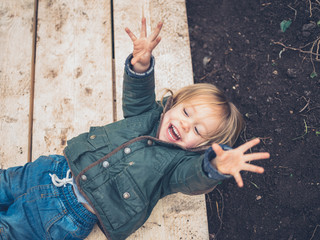 Happy little toddler on planks in garden