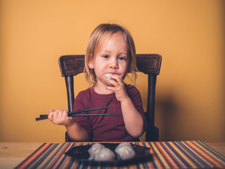 Little toddler eating dim sum with chop sticks