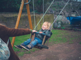 Toddler on swing getting a push from his mother
