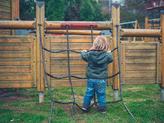 Toddler climbing rope in park