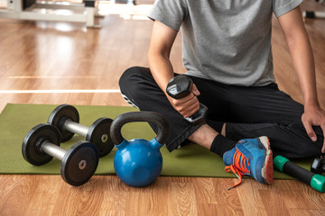 Closeup of  kettlebell , dumbbell and  sport man  sitting on mat, on the floor of a fitness center in the background - Image
