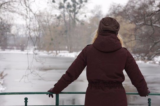 rear view of lonely woman standing on bridge gazing over frozen river in winter