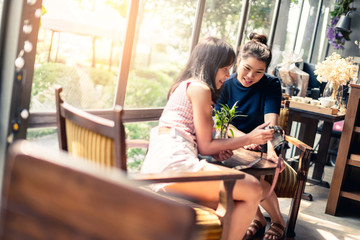 two beautiful asian woman friend happiness moment with selfie and enjoy conversation in coffeeshop with back window glass in garden