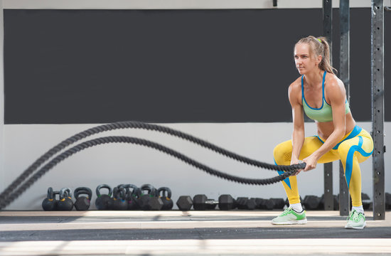Side view - Confident Sporty Blonde woman battling ropes during workout at the gym. Cross power training, fitness, sports. Place for text