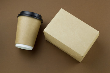 top view disposable paper cup with plastic lid and cardboard box mock up on brown background