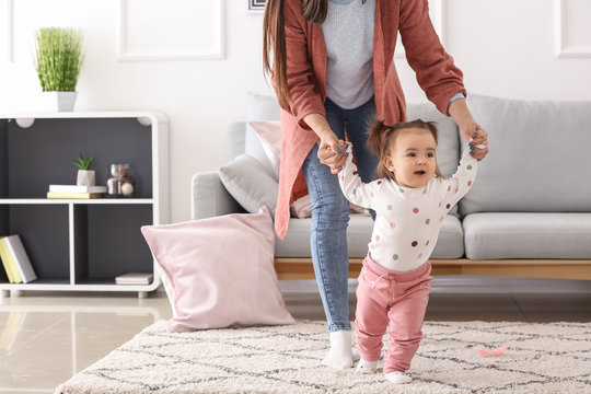 Young woman teaching her cute little daughter to walk at home