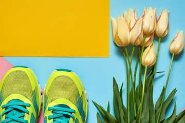 Pair of sport shoes and tulips bouquet on colorful pastel background. New sneakers on pink, blue and yellow paper, copy space. Overhead shot of running foot wear. Top view, flat lay