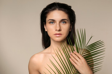 Portrait of beautiful young woman with natural makeup and tropical leaf on grey background
