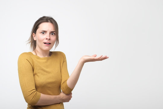 Woman throwing up hand and expressing misunderstanding