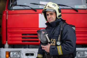 Picture of man fireman with mask in hands near fire truck