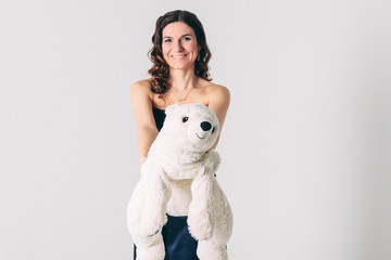 Young brunette woman in evening dress with polar bear toy on gra