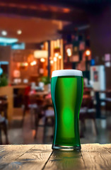 Glass of fresh cold green beer on a wooden bar counter in pub.
