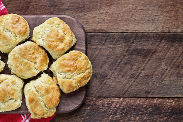 Fresh buttermilk southern biscuits or scones over a rustic wooden table shot from above. Top view.