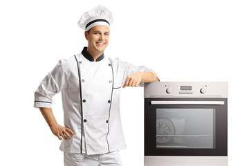 Smiling young male chef standing next to an oven