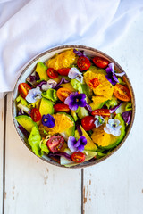 Bowl of mixed salad with avocado, tomatoes and edible flowers