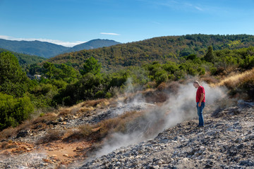 Italy, Tuscany, Colline Metallifere, Val di Cecina, Sasso Pisano, Valle delle Diavolo, hiker looking at geothermal field