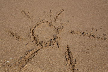 hand drawn sun shape on a sandy beach