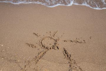 hand drawn sun shape on a sandy beach
