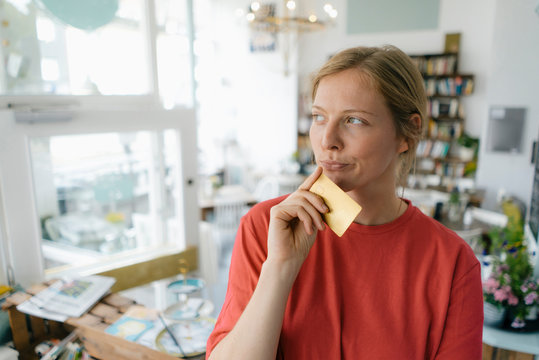 Young woman holding card in a cafe thinking