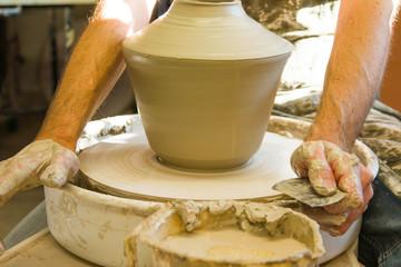 Detail of artist potter in the workshop sculpting ceramic vase