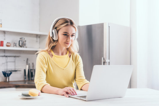 attractive blonde woman listening music in headphones while using laptop